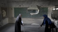 Palestinian teachers carry a table in a classroom at a government school in Gaza City on September 13, 2014, one day before children go back to school after a two-week delay caused by a seven-week war between Israel and Hamas. (photo credit: AFP/Mahmud Hams)