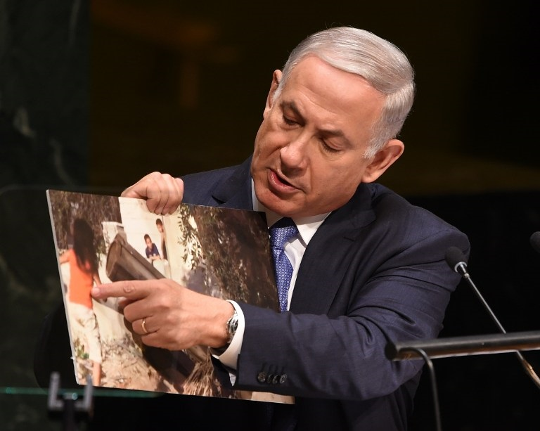 Prime Minister Benjamin Netanyahu holds up a photo of an alleged Hamas rocket near children as he addresses the 69th session of the United Nations General Assembly September 29, 2014 at the United Nations in New York. (photo credit: AFP PHOTO/Don Emmert)
