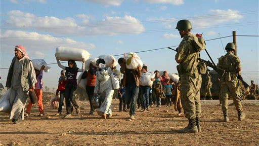 Turkish soldiers stand guard as Syrian refugees gather at the border in Suruc, Turkey, late Saturday, Sept. 20, 2014. (AP)