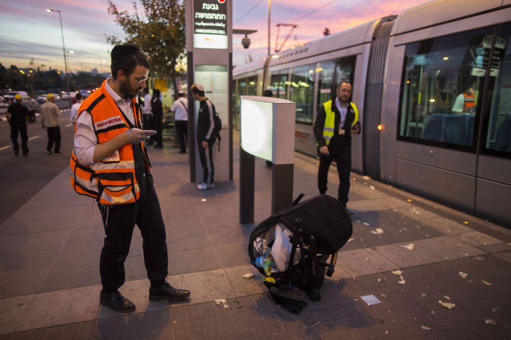 Police and rescue personnel near a baby stroller at the scene of a terror attack at a Jerusalem light rail station, by Ammunition Hill. October 22, 2014. (Photo credit: Yonatan Sindel/Flash90)