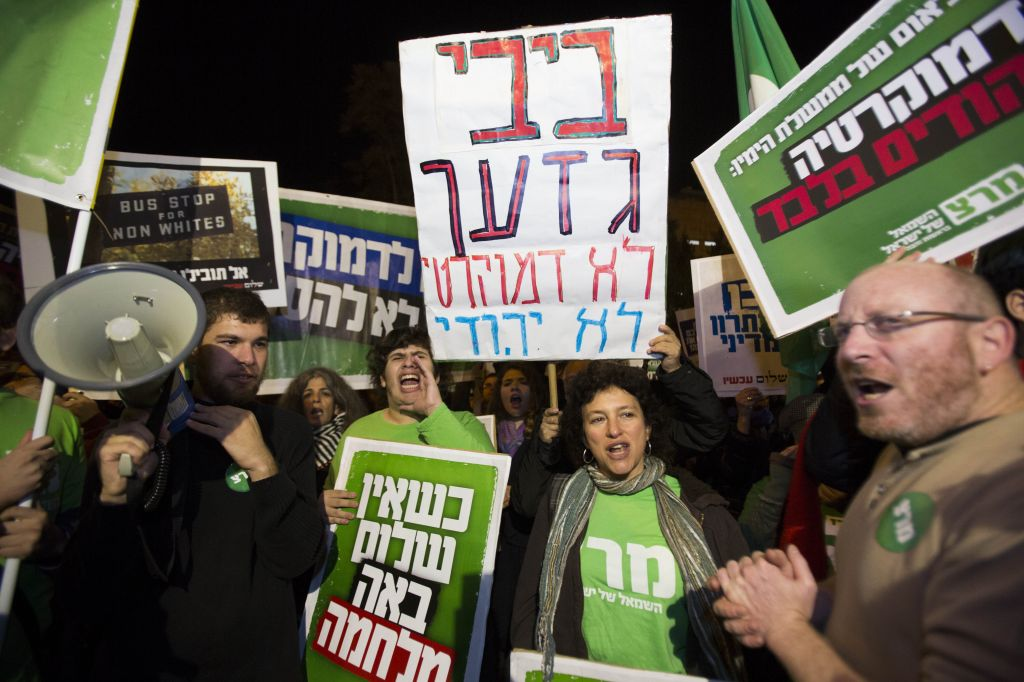"""Left-wing activists hold placards and flags as they protest against the """"Jewish state"""" bill near the Prime Minister residence in Jerusalem on November 29, 2014. Some of the placards call Benjamin Netanyahu a racist, and assert that he seeks democracy for Jews only. (Photo credit: Yonatan Sindel/Flash90)"""