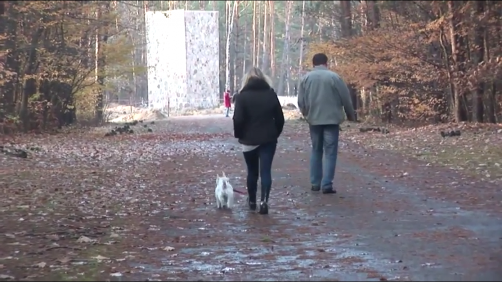 At the former Nazi death camp Sobibor, in eastern Poland, a visitor walks a dog through the area of the recently excavated gas chambers, in this Nov. 11, 2014 photo. (photo credit: Lena Klaudel)