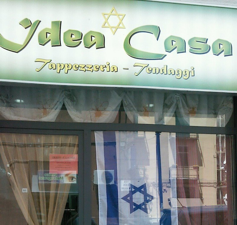 Antonio Calabrese's upholstery shop is adorned by a Star of David on its sign. He added the Israeli flag after the three murdered Israeli teens' bodies were discovered last summer. (courtesy)