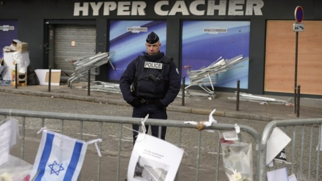 A policeman stands guard, on January 21, 2015, in front the Hyper Cacher kosher supermarket where jihadist gunman Amedy Coulibaly killed four Jewish men on January 9, 2015 in Paris. (AFP/Eric Feferberg)