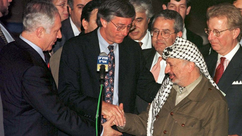 Prime Minister Benjamin Netanyahu, US envoy Dennis Ross, and Palestinian Authority president Yasser Arafat clasp hands after initialing an agreement on the partial withdrawal of Israeli troops from the West Bank after a meeting at Gaza's Erez Crossing, Wednesday, Jan 15, 1997. (photo credit: AP Photo/Nati Harnik)