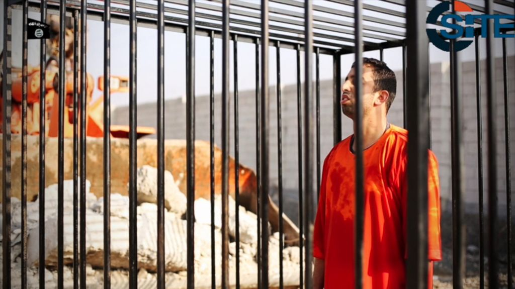 This still image made from video released by Islamic State group militants and posted on the website of the SITE Intelligence Group on Tuesday, Feb. 3, 2015, purportedly shows Jordanian pilot Lt. Muath al-Kaseasbeh standing in a cage just before being burned to death by his captors. The death of the 26-year-old pilot, who fell into the hands of the militants in December when his Jordanian F-16 crashed near Raqqa, Syria, followed a weeklong drama over a possible prisoner exchange. (photo credit: AP Photo/SITE Intelligence Group)