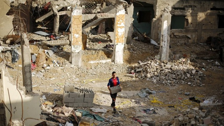 A Palestinian young man carries bricks amid the rubble of destroyed buildings in Beit Hanoun in the northern Gaza Strip, March 4 2015. (AFP/Mohammed Abed)