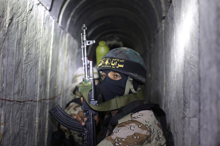 Palestinian militants from the Islamic Jihad's armed wing, the al-Quds Brigades, squat in a tunnel used for ferrying rockets and mortars back and forth in preparation for the next conflict with Israel, as they take part in military training in the south of the Gaza Strip on March 3, 2015. (AFP/Mahmud Hams)