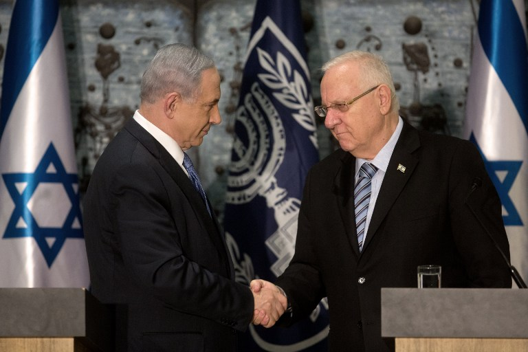 Prime Minister Benjamin Netanyahu (L) shakes hands with Israeli President Reuven Rivlin as he is formally given the task to form the next government, at the president's residence in Jerusalem on March 25, 2015. (photo credit: AFP PHOTO / MENAHEM KAHANA)