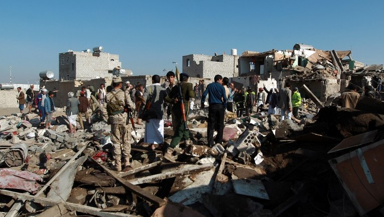 Yemeni Houthi rebels and members of the security forces loyal to the Shiite movement inspect the damage at the scene of a Saudi airstrike targeting the group, which controls Sanaa near the airport in the Yemeni capital, on March 26, 2015. (photo credit: Mohammed Huwais/AFP)