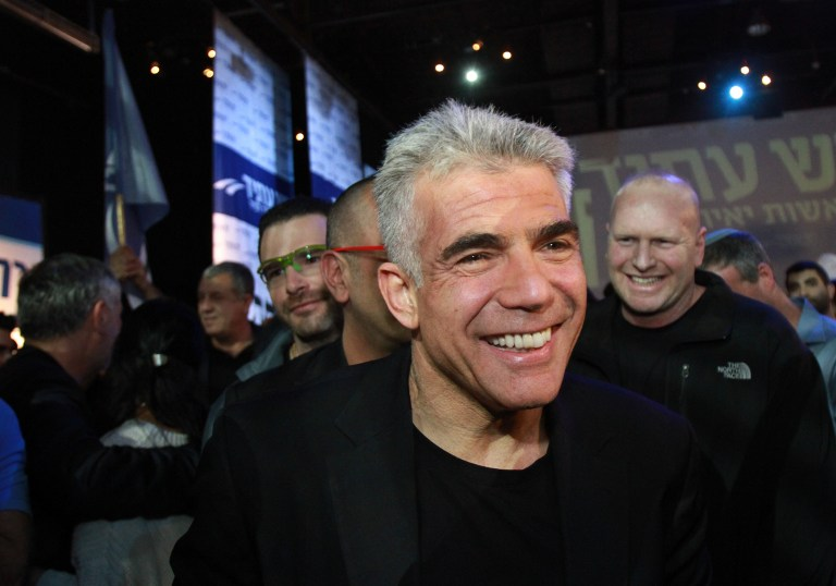 Israeli MP and chairperson of the centrist Yesh Atid party, Yair Lapid celebrates with supporters early on January 18, 2015 at his party headquarters in Tel Aviv. (photo credit: AFP / GIL COHEN-MAGEN)