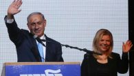 Benjamin Netanyahu and his wife, Sara, wave to supporters as exit polls come in on March 17. Menahem Kahana/AFP/Getty Images