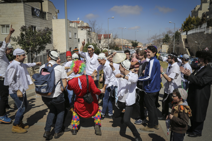 Israelis dressed up in costumes celebrate the Jewish holiday of Purim on the streets of the Jewish settlement of Efrat, West Bank, on March 5, 2015. (photo credit: Gershon Elinson/Flash90)