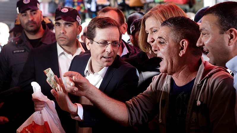 Isaac Herzog and Tzipi Livni seen during a campaign tour at Shuk Hacarmel market in Tel Aviv, March 12, 2015. (photo credit: Amir Levy/Flash90)
