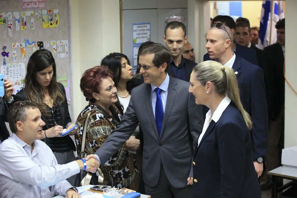 Zionist Union leader Isaac Herzog accompanied by his wife Michal prepares to cast his vote in Tel Aviv, Israel, Tuesday, March 17, 2015. (photo credit: AP Photo/Ariel Schalit)