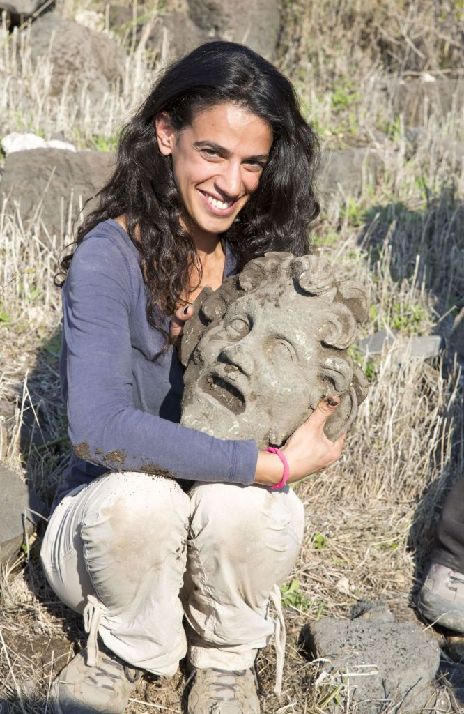 A woman holds a larger-than-life bronze mask of Greek god Pan, found by Haifa University archeologists in early 2015. (photo credit: Courtesy Haifa University)