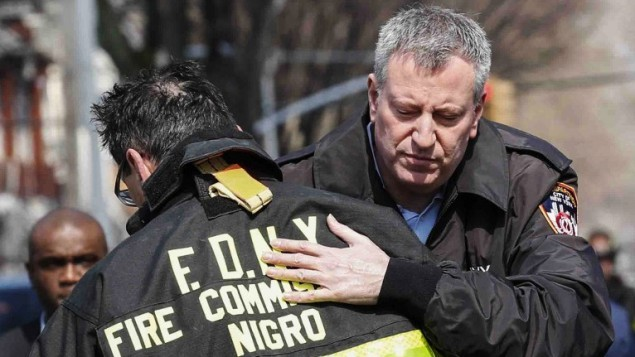 Le Maire de New York Bill de Blasio enlace le commandant des pompiers de New York Daniel Nigro  devant la maison en feu dans le quartier Midwood à Brooklyn le 21 mars 2015  (Crédit photo: Kena Betancur / Getty Images / AFP)