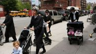 Members of the Orthodox Jewish community walk down a street in a Brooklyn. Getty Images