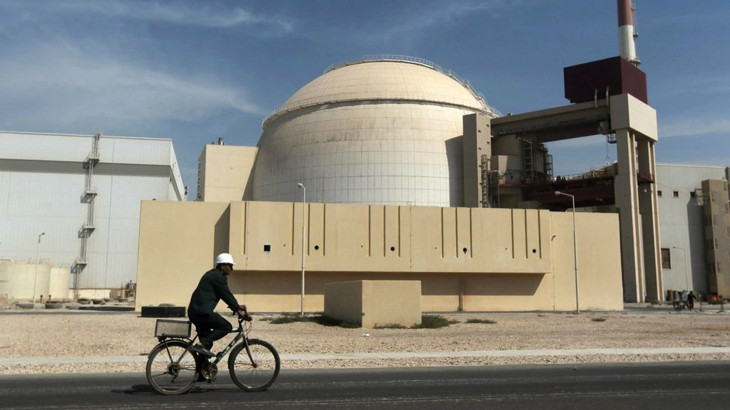 A worker rides a bicycle in front of the reactor building of the Bushehr nuclear power plant, just outside the southern city of Bushehr, Iran, on October 26, 2010. (AP/Mehr News Agency, Majid Asgaripour, File)