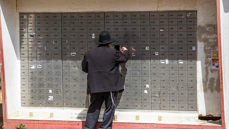 Illustrative photo: An ultra orthodox man checks his mail box, in Beitar Illit on March 17, 2015. (Photo credit: Nati shohat/Flash90)