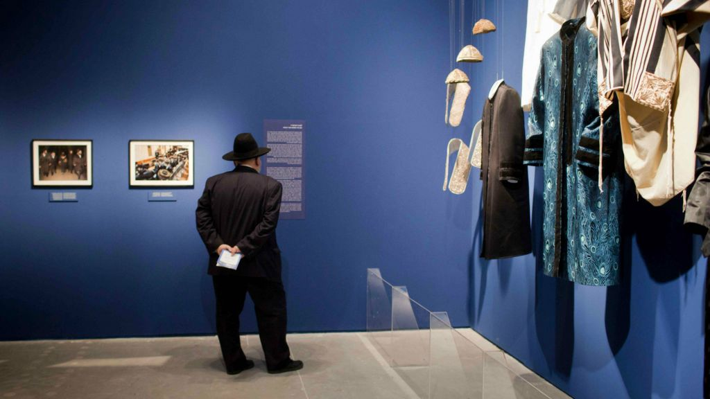 """Visitors looking at photographs displayed at the Israel Museum exhibition """"A World Apart Next Door: Glimpses into the life of Hasidic Jews"""" in Jerusalem on June 20, 2012. The ethnographic exhibition highlights facets of the culture of the Hasidic Jews. (Photo credit: Yonatan Sindel/Flash90)"""