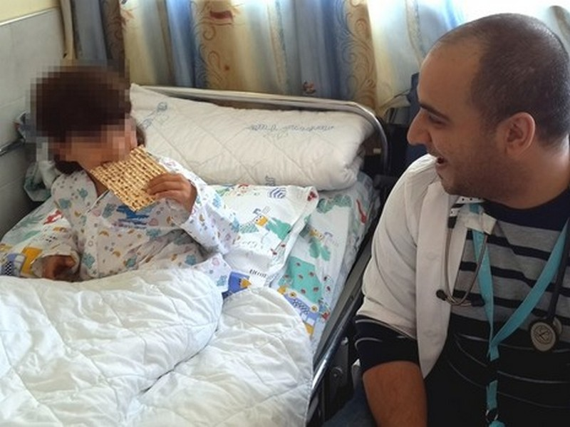 A Syrian boy hospitalized in Israel has his first taste of matza on Tuesday, April 7, 2015 (photo credit: courtesy Ziv Hospital)