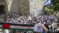 """Palestinian women hold a scarf bearing the Palestine name as Israeli youths carry their national flag in the """"flag march"""" through Damascus Gate in Jerusalem's Old City during celebrations for Jerusalem Day on May 17, 2015. (AFP Photo/Jack Guez)"""