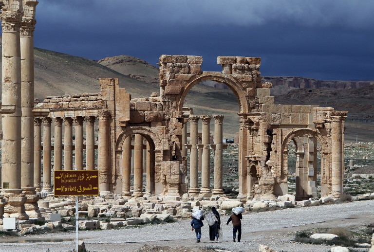 Syrian citizens walking in the ancient oasis city of Palmyra on March 14, 2014. (AFP/JOSEPH EID)