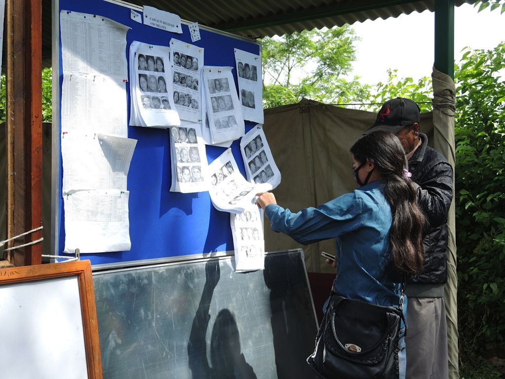 Relatives check a list of photos of patients outside the waiting tent at the Nepali military field hospital, May 4, 2015.(photo credit: Melanie Lidman / Times of Israel)