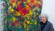 "Arline Jacoby in front of her painting, ""Color Burst,"" at the RIVAA Gallery"