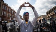 A man makes a heart shape with his hands during a protest in Baltimore, Maryland. Getty Images