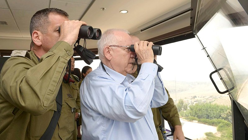 president Reuven Rivlin look through binoculars during his visit in the Northern district border of Israel on May 27, 2015. (Mark Neyman/GPO)