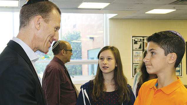 Seventh-grader Chana Berkman and sixth-grader Evan Block talk to Mr. Metzl. Daniel Jaye, the school's director of academic affairs, is in the background.