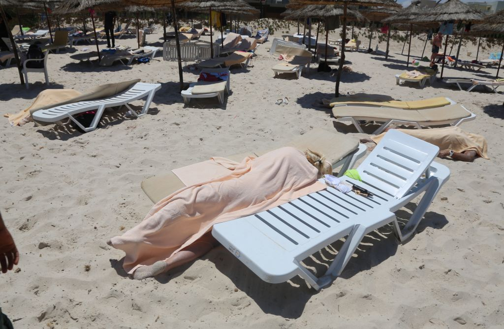 Bodies are covered on a Tunisian beach, in Sousse, Friday June 26, 2015. A young man unfurled an umbrella and pulled out a Kalashnikov, opening fire on European sunbathers in an attack that killed at least 28 people. (Jawhara FM via AP)