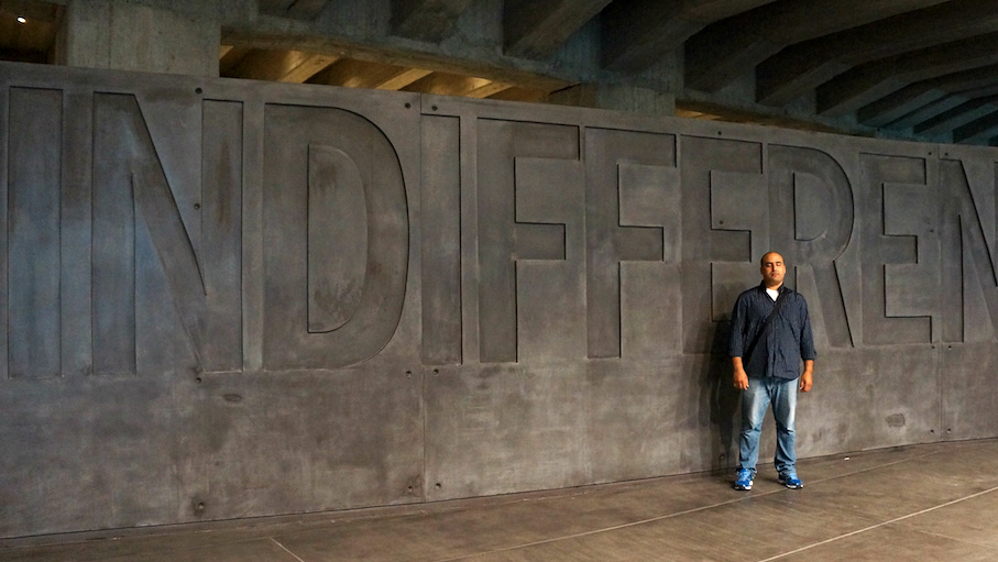 Moroccan immigrant Adil Khabi has lived in Italy for the past 13 years. Today he volunteers at Milan's Holocaust Memorial where he is pictured on June 22, 2015 against its Wall of Indifference, to help with the African refugees sheltered there. (Rossella Tercatin/The Times of Israel)