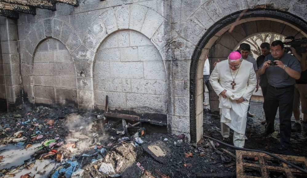A priest inspects the damage caused to the Church of the Multiplication at Tabgha, on the Sea of Galilee, in northern Israel, which was set on fire in what police suspect was an arson attack, June 18, 2015. (Basel Awidat/Flash90)