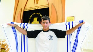 A teenager in Nir HaEmek wears a WIZO shirt as he prepares to wrap himself in his tallit before davening.