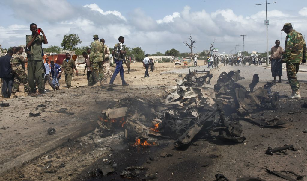Somali soldiers stand near the wreckage at the scene of a suicide car bomb attack which targeted a convoy of foreign officials, in Mogadishu, Somalia Wednesday, June 24, 2015. (AP Photo)