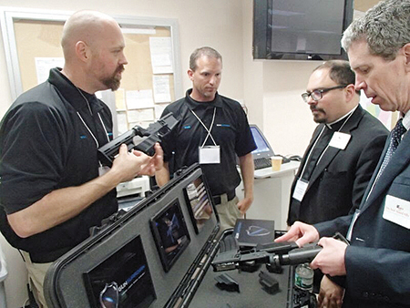 Religious leaders and police officers look at smart gun prototypes at a show exhibiting the new technology.