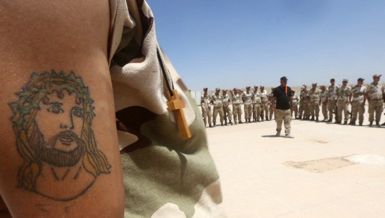 A tattoo of Jesus Christ is seen on the arm of an Iraqi Christian volunteer from the northern embattled Mosul governorate, as he attends a training session at a base in Baghdad airport on July 1, 2015. (AFP PHOTO / AHMAD AL-RUBAYE)
