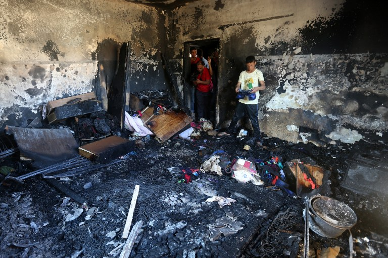 Palestinians look at the damage after a house was set on fire and a baby killed, allegedly by Jewish terrorists, in the West Bank village of Duma, on July 31, 2015. (AFP/Jaafar Ashtiyeh)