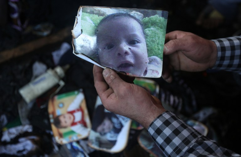 A man shows a picture of 18-month-old Palestinian toddler Ali Saad Dawabsha who died when his family house was set on fire by alleged Jewish extremists in the West Bank village of Duma on July 31, 2015. (AFP PHOTO / JAAFAR ASHTIYEH)