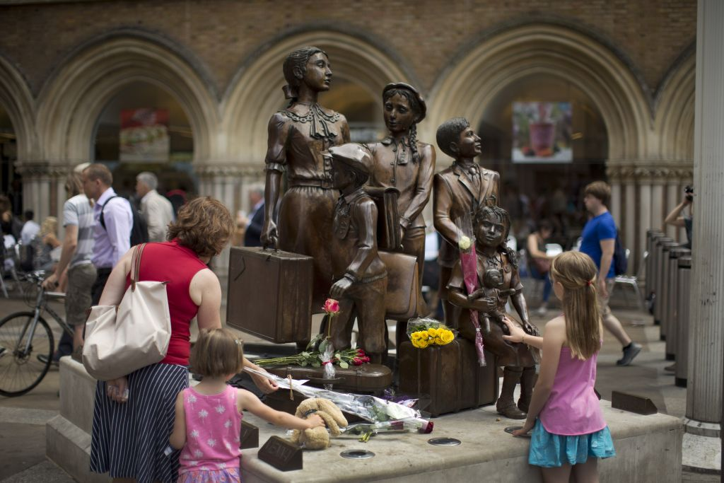 People look at flowers laid in memory of Britain's Sir Nicholas Winton on German-born Jewish sculptor Frank Meisler's 'Kindertransport' (German for children transport) memorial statue outside Liverpool Street Station in London, Thursday, July 2, 2015. (AP Photo/Matt Dunham)