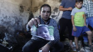 A relative holds up a photo of a one-and-a-half year old boy, Ali Dawabsha, in the family house torched in a suspected attack by Jewish terrorists in Duma village near the West Bank city of Nablus, Friday, July 31, 2015. The boy died in the fire, his four-year-old brother and parents were badly hurt. (AP Photo/Majdi Mohammed)
