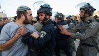 Israeli security forces scuffle with settlers who had barricaded themselves in an attempt to prevent the demolition of illegally constructed buildings, at the Jewish settlement of Beit El, near the West Bank town of Ramallah, on July 28, 2015 (Nati Shohat/FLASH90)