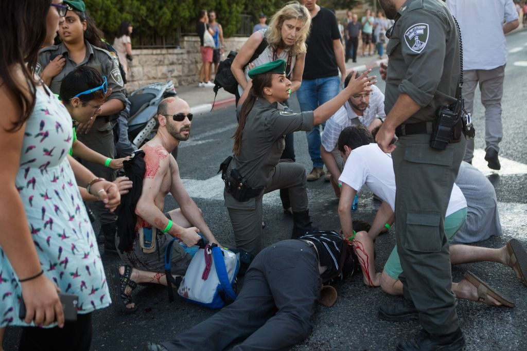 Police and rescue personnel tend to young Israelis wounded in a stabbing attack at the annual pride parade in Jerusalem on July 30, 2015. (Photo by Miriam Alster/FLASH90)