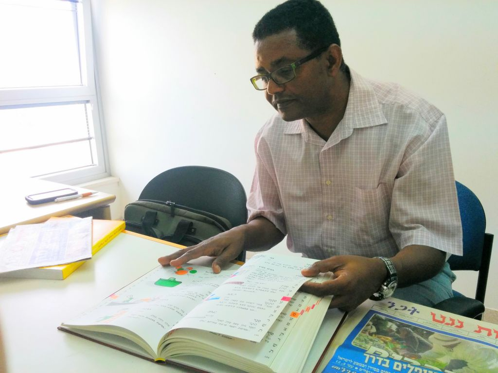Dr. Anbessa Teferra, a professor of Semitic languages at Tel Aviv University, with an Amharic-Hebrew pictorial dictionary he edited. (Ilan Ben Zion/Times of Israel staff)