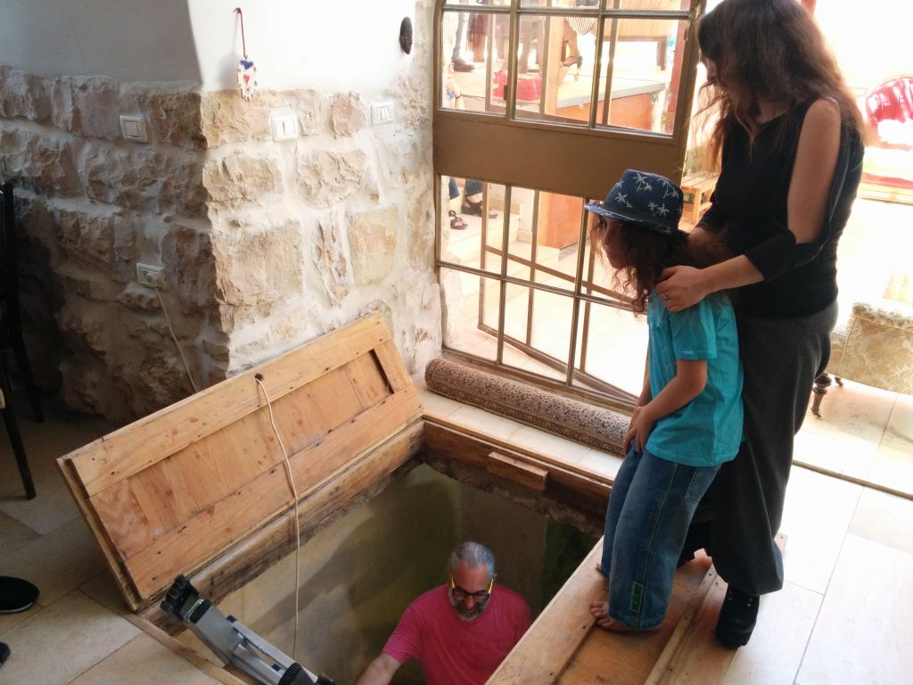 The Shimshoni family stands by a first century Jewish ritual bath in their home in Ein Karem, on July 1, 2015. (Ilan Ben Zion/Times of Israel staff)