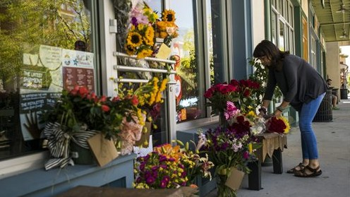 A woman leaves a bouquet of flowers at a makeshift memorial for store co-owner Jillian Johnson at Red Arrow Workshop in River Ranch in Lafayette, La., Friday, July 24, 2015 (Paul Kieu/The Daily Advertiser via AP)