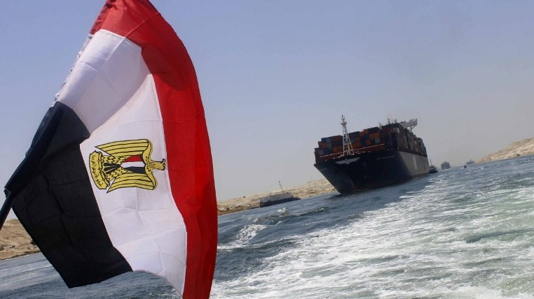 An Egyptian flag flutters as a container ship crosses the new waterway of the Suez canal on July 23, 2015, in the Egyptian port city of Ismailia, east of Cairo (AFP/STR)